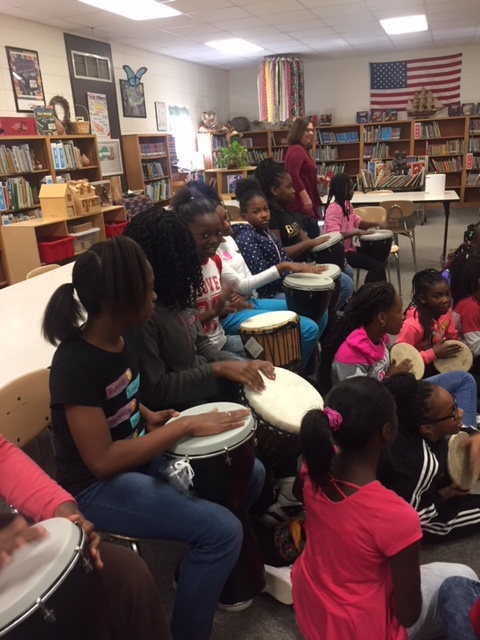 Salem's 4th and 5th grade girls playing djembes int eh library.